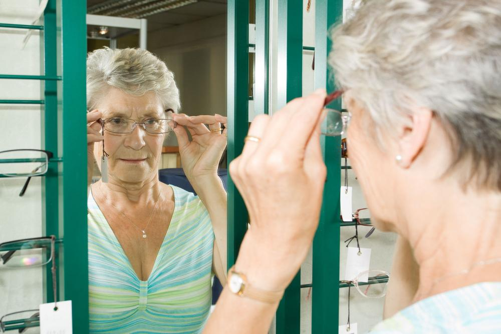 Woman looking in the mirror with her new glasses